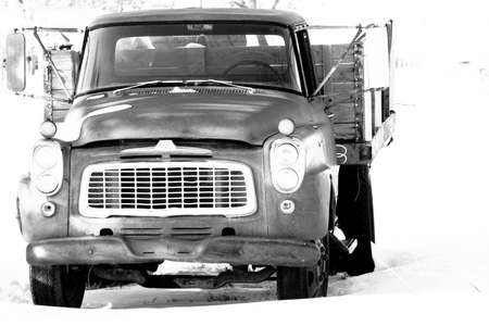 A black and white image of an old pick-up truck abandoned in the winter snow.