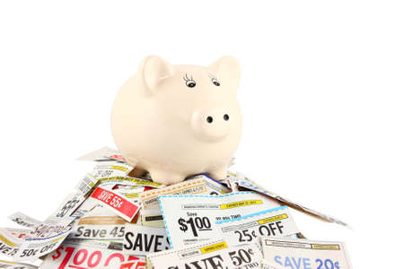 One ceramic piggy bank standing on top of a pile of coupons.