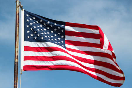An American flag blowing in the wind on a bright sunny day