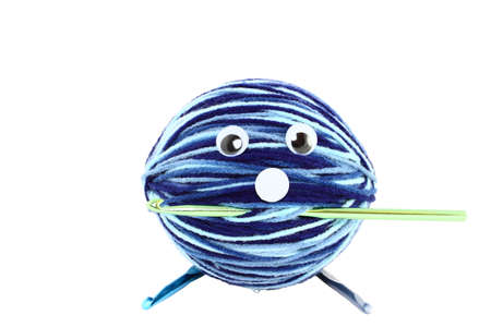 A large ball of yarn with plastic eyes and crochet hooks