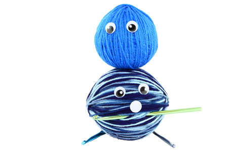 Two balls of blue yarn with plastic eyes to make funny faces