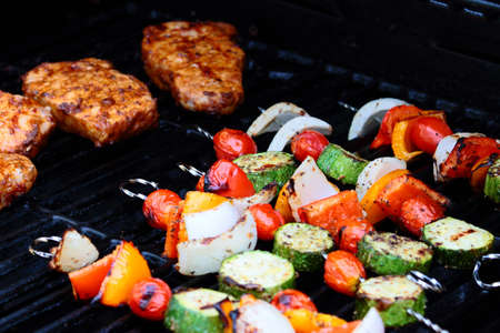 Colorful vegetable skewers and chops cooking on a grill.