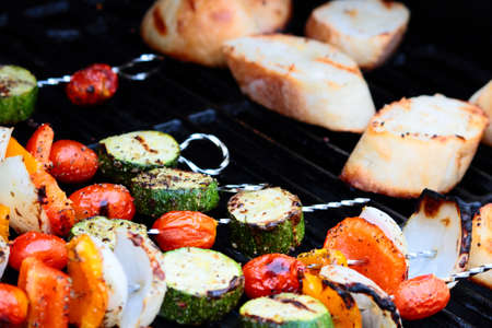 Flavorful vegetable skewers and fresh bread on grill.