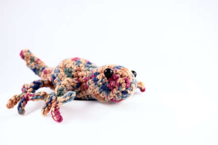 A handcrafted toy gecko crocheted from colorful yarn