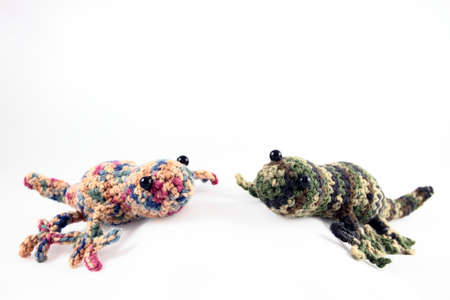 Two handcrafted toy geckos crocheted from colorful yarns