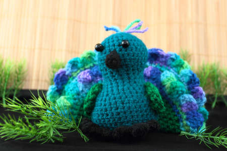 A handcrafted toy peacock crocheted from blue and green shades of yarn  Stock Photo