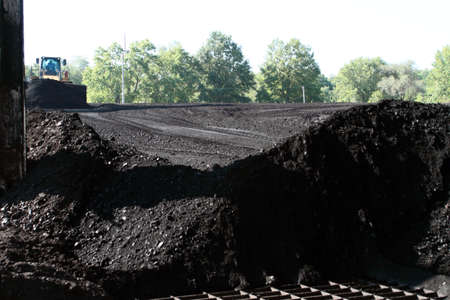 front end loader: Front End Loader Driving Over Piles Of Sub-Bituminos Coal Stock Photo