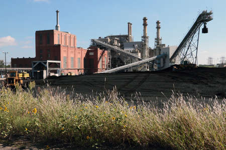 heap: A Small Coal Fired Power Plant with Coal Yard and Wildflowers. Stock Photo