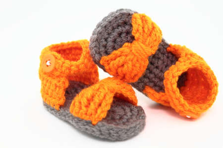 A Pair Of Handcrafted Baby Sandals In Orange And Gray Stock Photo