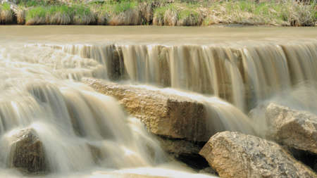 Small Waterfall Tumbling Over Stones Across A River Stock Photo