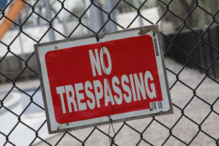 trespassing: Red No Trespassing Sign On Fence