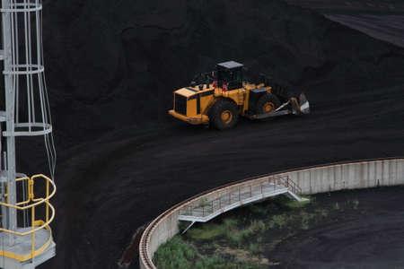 Yellow Dozer Moving Black Coal
