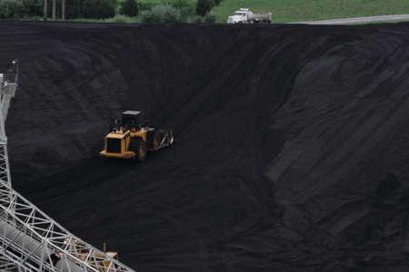 Bulldozer Pushing Coal Up Hill Stock Photo
