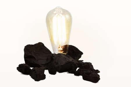 edison: Edison Style Light Bulb In Coal Pile Stock Photo