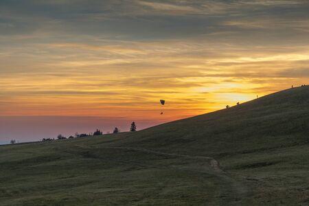 Para gliders starting flight during sunset