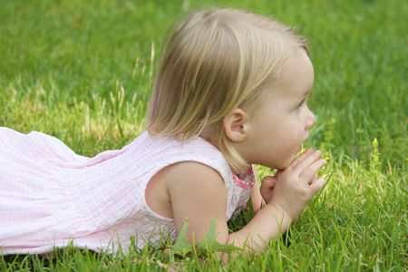 child laying on grass
