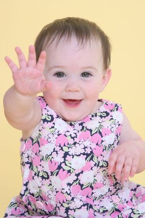 exuberance: girl smiling and waving hello