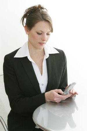 dialing: woman dialing cell phone sitting at bistro table Stock Photo