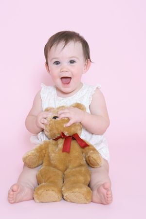 contentment: girl playing with teddy bear
