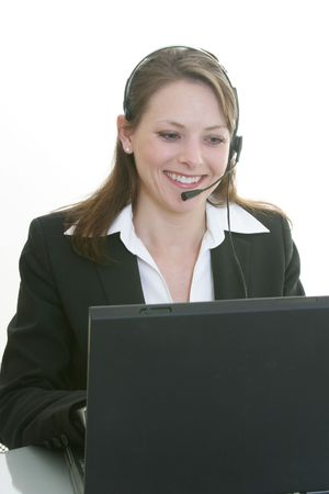 woman with headset typing on a laptop Stock Photo