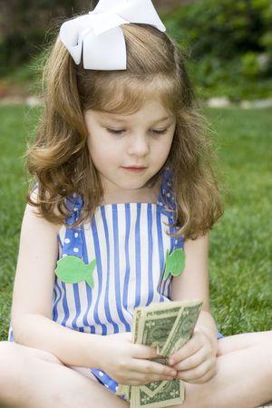 お金の束を持つ表現力豊かな少女