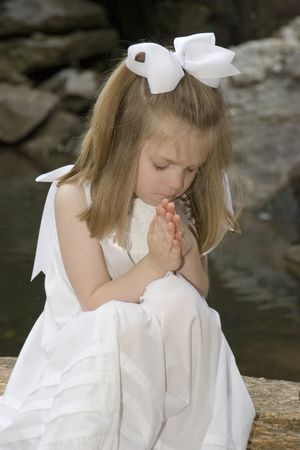 a righteous person: Little girl praying outside Stock Photo