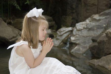 jesus adolescent: Little girl praying outside Stock Photo