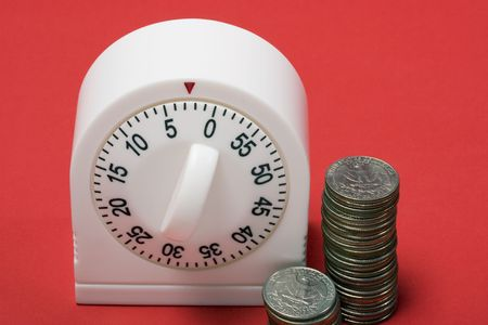 ticking away: close-up of egg timer running out of time with quarters