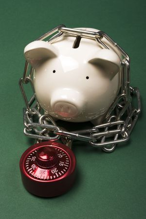 Piggy bank with a red combination lock and chain photo