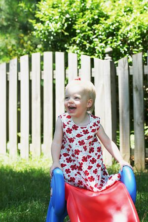 Little girl playing on a slide outside in the summer Stock Photo - 592596