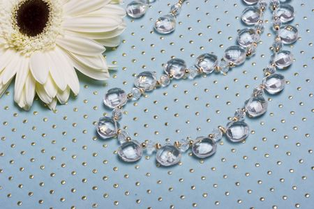 A bead necklace with clear stones on blue background