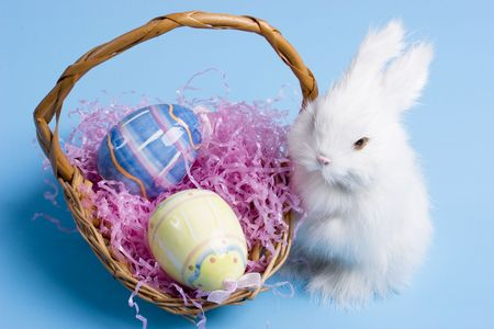 easter bunny with a wooden basket and two easter eggs photo