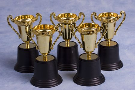 awarding: Five gold trophies on a blue background