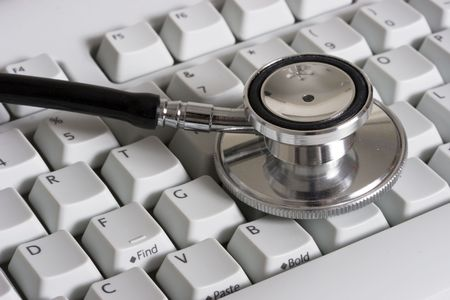 computerize: close-up of a computer white keyboard with stethoscope - computerized healthcare