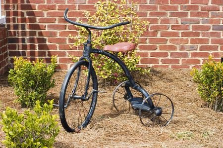 An antique bicycle in from of a brick wal