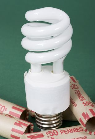 An energy efficient light bulb with rolls of pennies Stock Photo - 842009