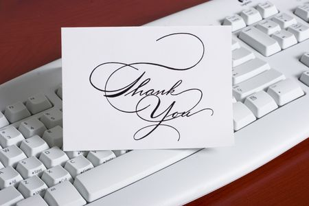 close-up of a computer white keyboard with thank you\ cards