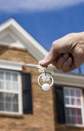 Woman holding a key for a house on a keychain in front of a brick house