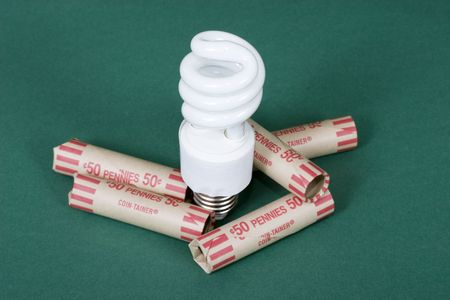 An energy efficient light bulb surrounded penny coin holders Stock Photo - 843132