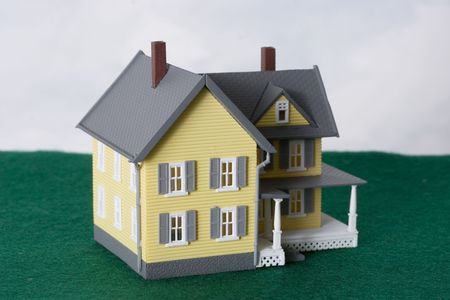 downpayment: two story yellow house on green and blue background with copy space Stock Photo