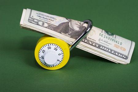 Yellow combination lock with twenty dollar bills photo