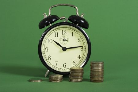 A row on coins with increasing value with an alarm clock photo