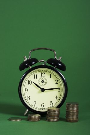 compounding: A row on coins with increasing value with an alarm clock Stock Photo