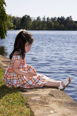 kids dress: A little girl sitting by a lake