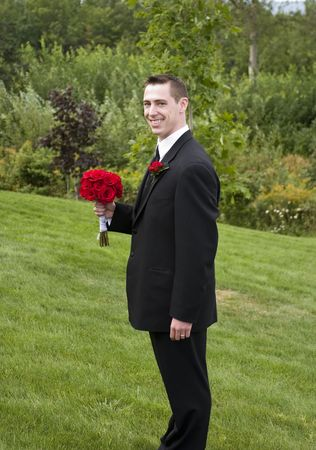 The groom holding a red rose bouquet – humorous photo Stock Photo