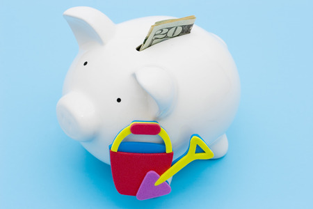 loaning: A piggy bank with a twenty dollar bill with a beach bucket and shovel Stock Photo
