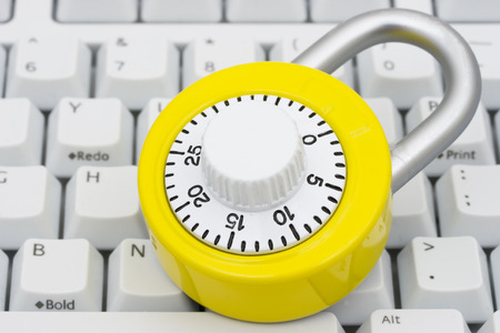 A bright yellow combination lock on a keyboard Stock Photo - 1463449