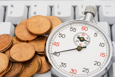 technology transaction: A stopwatch with pennies on a white keyboard