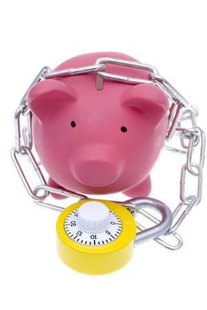 A pink piggy bank with chains and a bright yellow combination lock with some pennies isolated on a white background photo