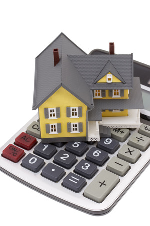 in escrow: A house on top of a calculator isolated on a white background